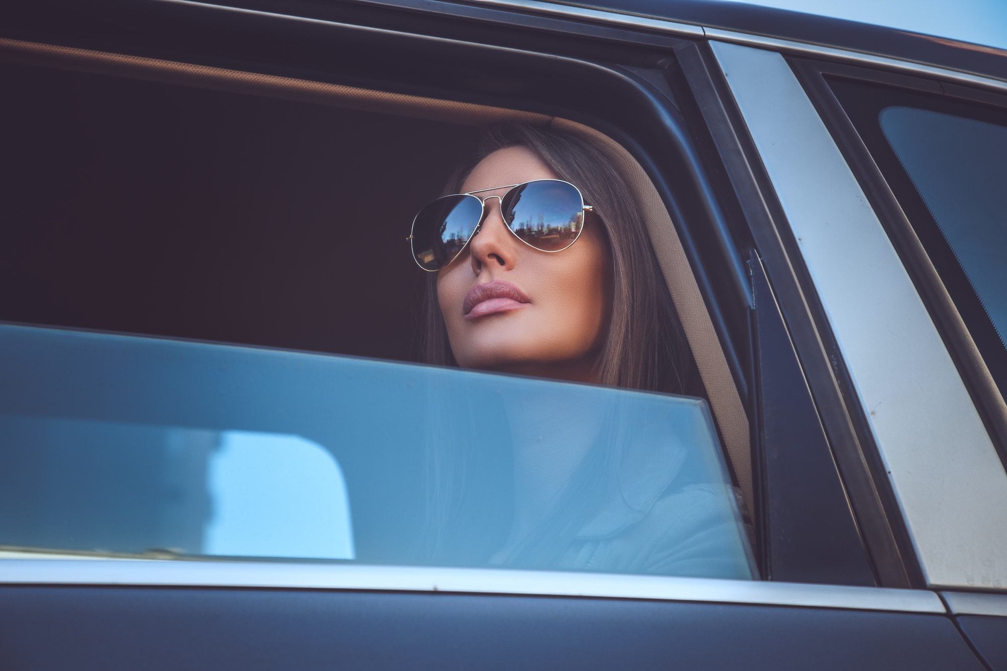 A woman in sunglasses looking outside